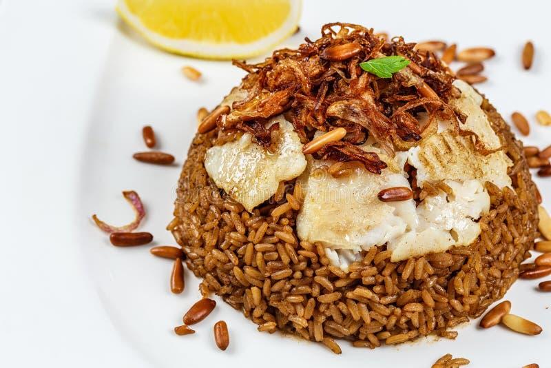 Plat de poissons du Moyen-Orient traditionnels et de riz frit avec les pignons frits images stock