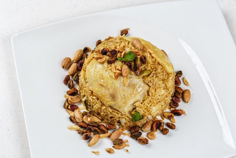 Plat de poissons du Moyen-Orient traditionnels et de riz frit avec les pignons frits photos stock