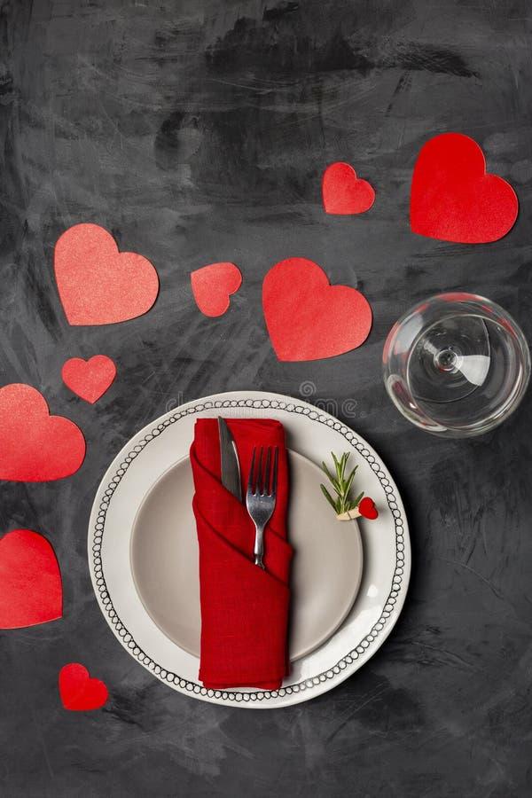 Plat de portion de Saint-Valentin avec la fourchette, le couteau et les coeurs rouges formés au fond noir photos stock