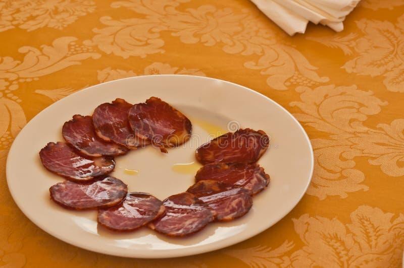 Plat de salami traité et coupé en tranches avec l'huile d'olive en tant qu'appareillement pour un événement d'échantillon de vin  images libres de droits