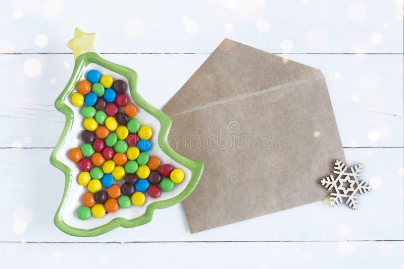 Plat de sapin de Noël avec les sucreries colorées et une enveloppe pour des souhaits photo stock