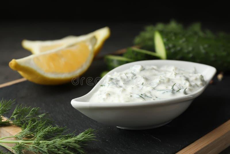 Plat de sauce à Tzatziki avec les tranches, le concombre et l'aneth de citron photo stock