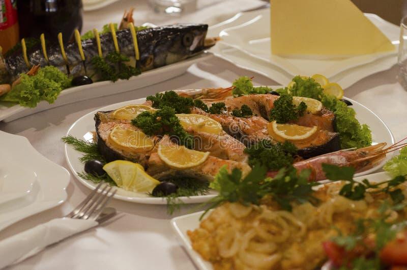 Plat de steak de saumon cuit garni de persil au citron et de crevettes 2 photos libres de droits