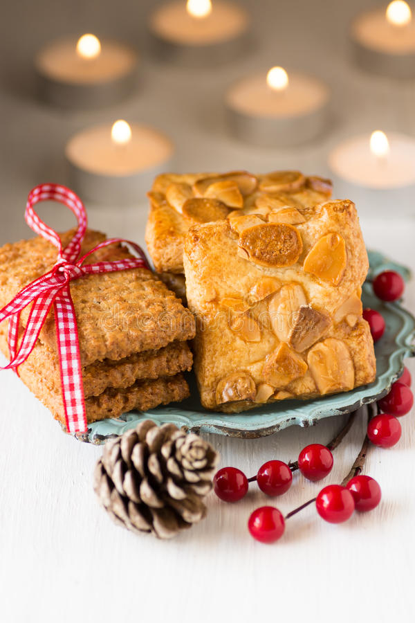 Plat de vintage de l'ARO de biscuits de Noël avec des baies de houx et cône de pin sur la table blanche image stock