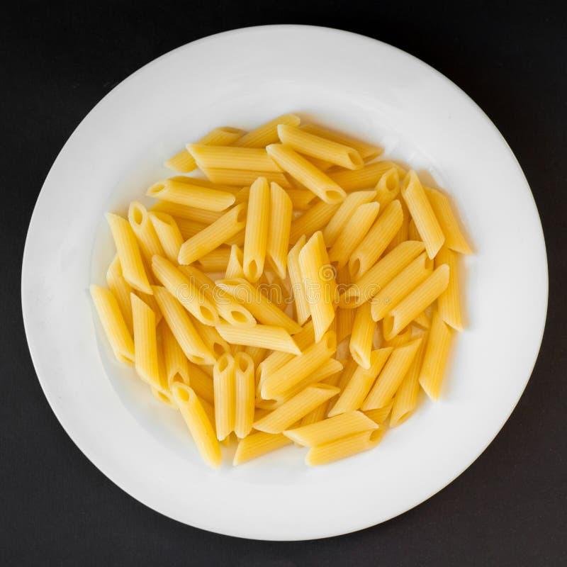 Plat de vue supérieure des macaronis de pâtes sur le fond noir photographie stock libre de droits