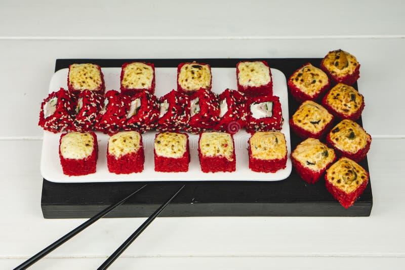 Plat den röda uppsättningen för sushirulle på vit och den mörka tabellen arkivbilder