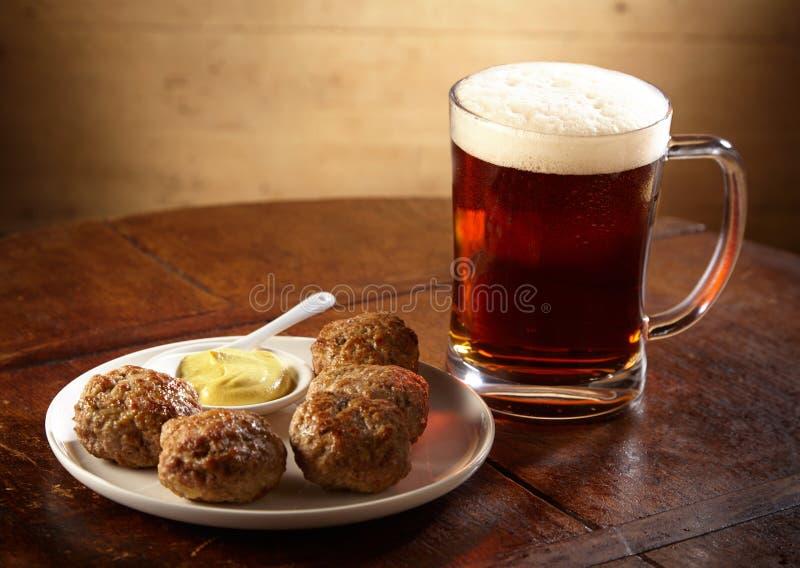Plat des boulettes de viande épicées servies avec de la bière images stock
