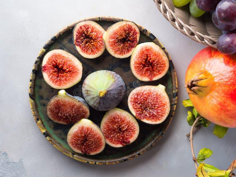Plat des figues, des raisins et de la grenade pourpres image libre de droits