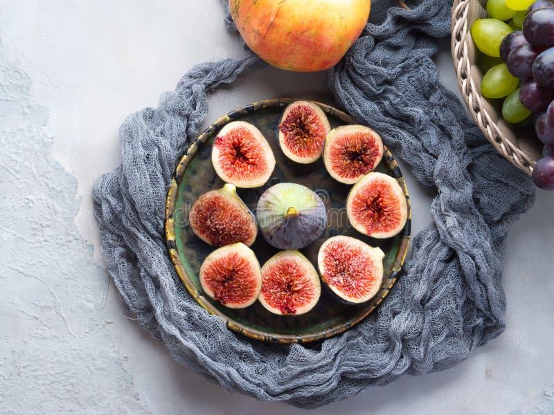 Plat des figues, des raisins et de la grenade pourpres images libres de droits