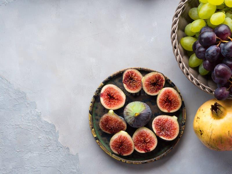 Plat des figues, des raisins et de la grenade pourpres photo stock