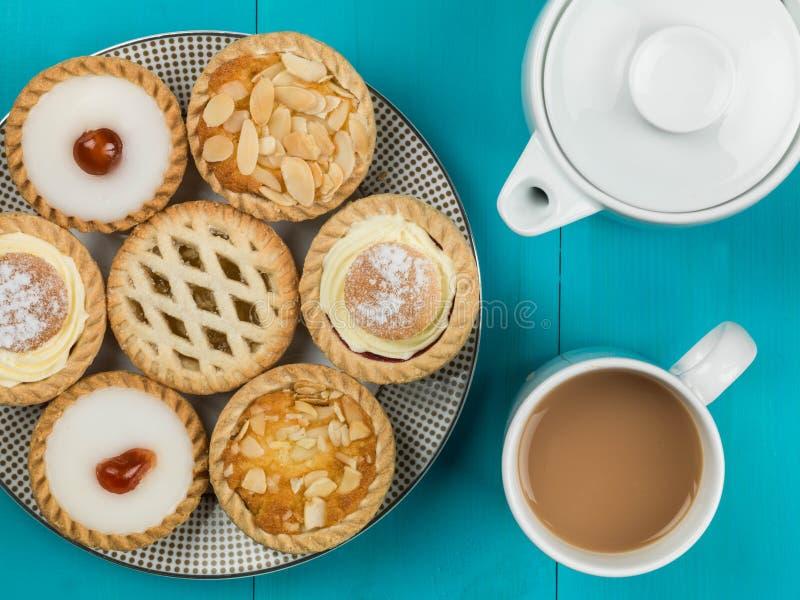 Plat des gâteaux ou des tartes assortis de personne avec un pot de thé photo stock