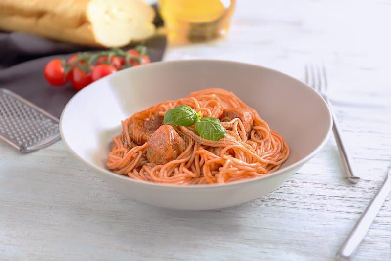 Plat des pâtes délicieuses avec la sauce de viande et tomate sur la table en bois blanche photographie stock
