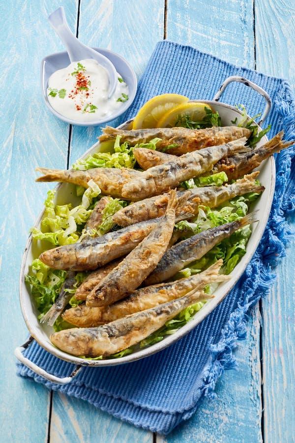 Plat des sardines frites fraîches saisonnières sur la laitue photo stock