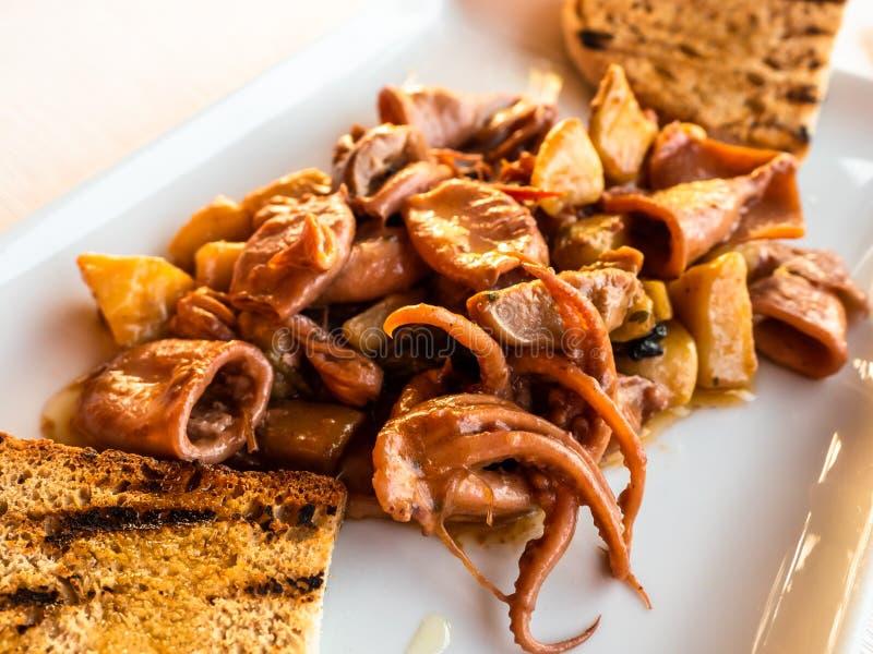 Plat des seiches et du poulpe avec du pain grillé image libre de droits