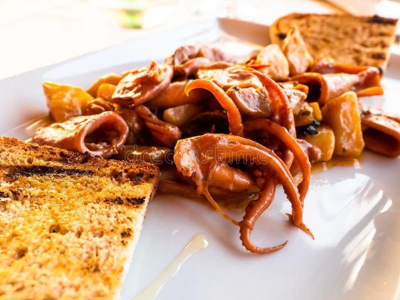 Plat des seiches et du poulpe avec du pain grillé photo stock