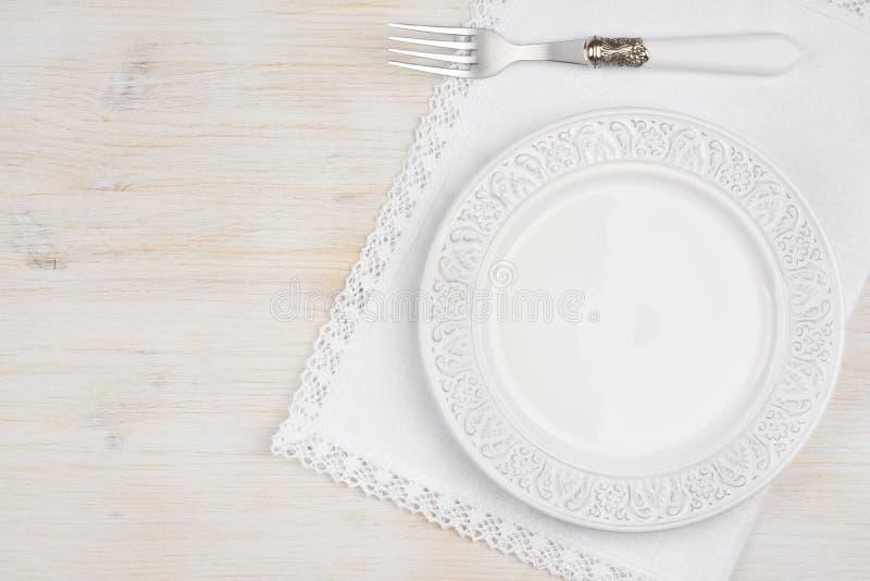Plat en céramique blanc avec la fourchette au-dessus du placemat sur la table en bois photographie stock