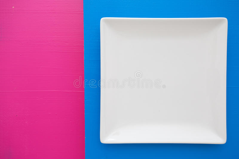 Plat en céramique blanc vide dessus au-dessus du fond bleu et rose, squar photos libres de droits
