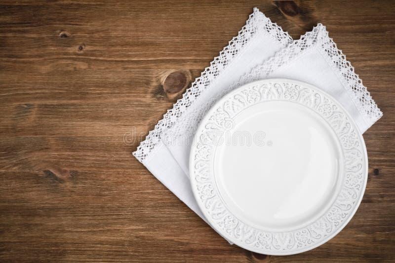 Plat en céramique de vintage au-dessus de serviette de table sur le fond en bois foncé photographie stock