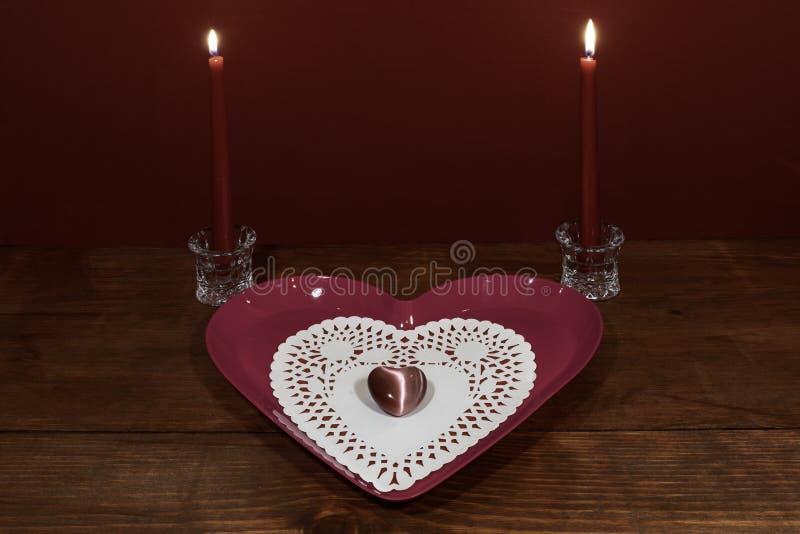 Plat en forme de coeur rose avec le dollie et pierre gemme, deux bougies rouges dans les supports en cristal sur la table en bois photos libres de droits