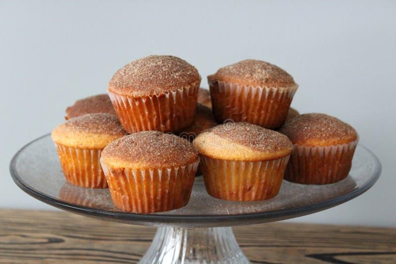 Plat en verre simple de gâteau montrant les petits pains cuits au four frais de carotte avec du sucre de cannelle sur chacun images stock