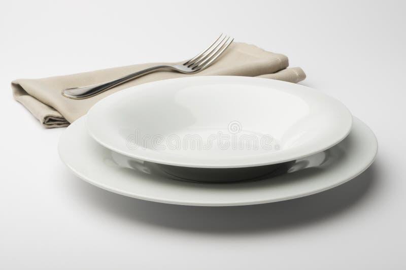 Plat et cuvette blancs ronds vides avec la serviette et la fourchette photo stock