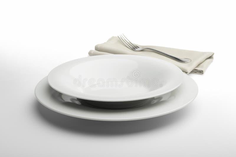 Plat et cuvette blancs ronds vides avec la serviette et la fourchette images libres de droits