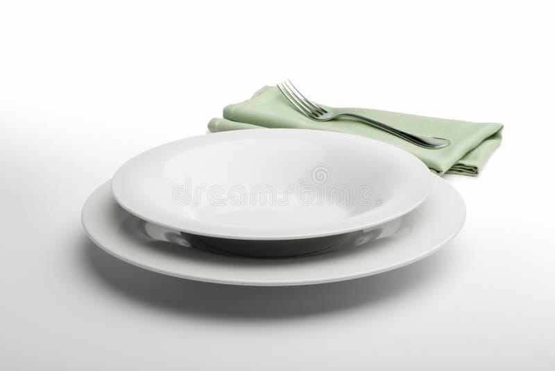 Plat et cuvette blancs ronds vides avec la serviette et la fourchette photographie stock