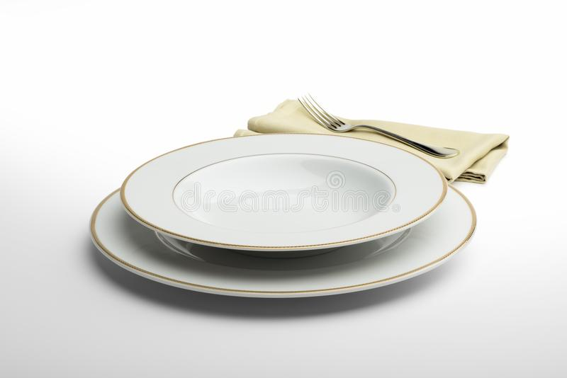 Plat et cuvette blancs ronds vides avec la serviette et la fourchette photos stock