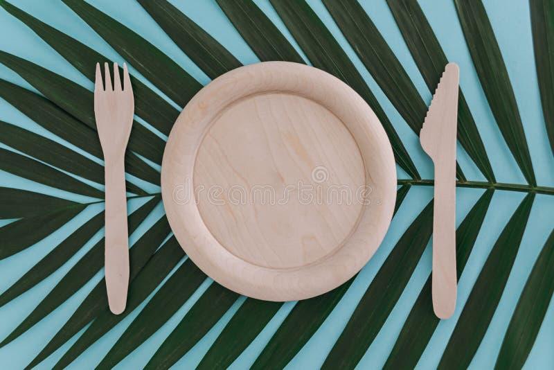 Plat, fourchette et couteau vides en bois sur le fond en feuille de palmier sur le bleu Concept de rebut z?ro image stock