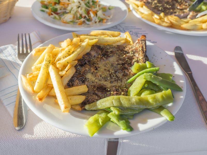 Plat haut étroit avec le repas grec fait maison traditionnel, le bifteck grillé de porc avec des pommes frites et les haricots ve photographie stock libre de droits