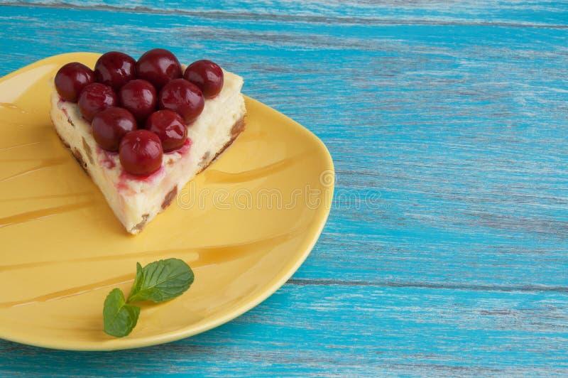 Plat jaune avec un morceau de gâteau au fromage images stock