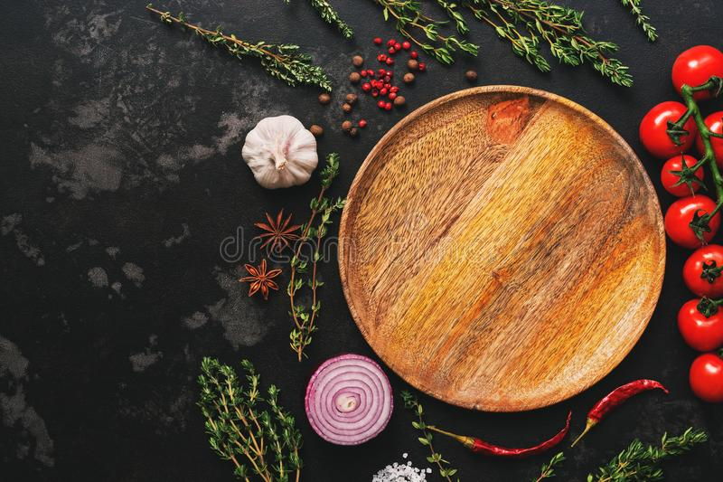 Plat, légumes, épices et herbes en bois vides étendus par appartement sur le fond en pierre foncé Tomates, thym, ail, grain de po photos stock