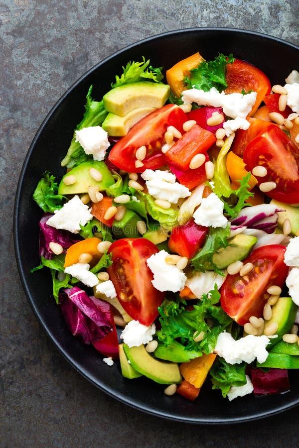 Plat légumes, salade avec l'avocat, poivre, tomate, mélange italien, laitue fraîche, feta et pignons Nourriture saine photo libre de droits