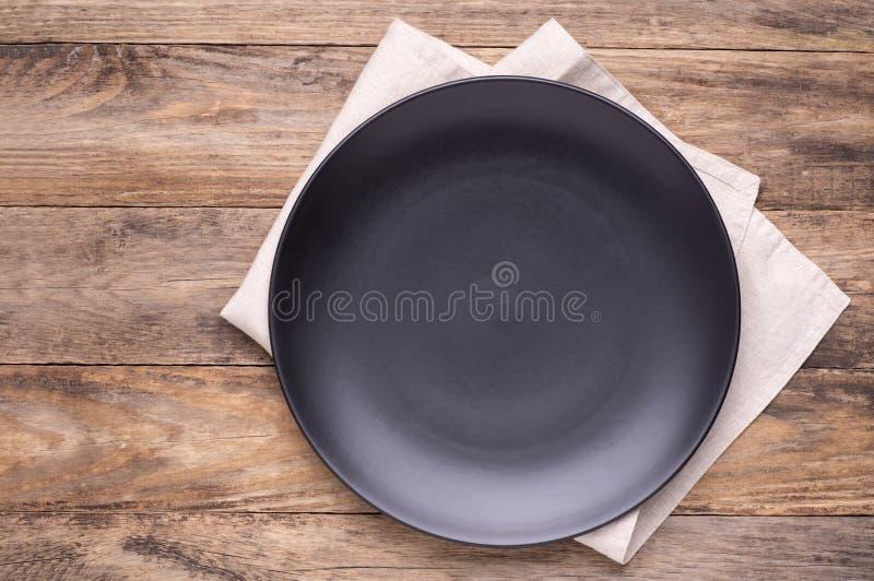 Plat noir vide avec la serviette sur la vieille table en bois image stock