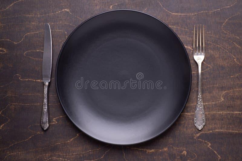 Plat noir vide et couverts argentés sur la table en bois foncée photographie stock