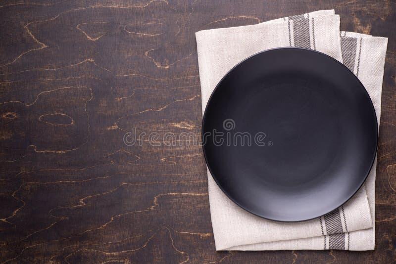 Plat noir vide sur la table en bois foncée images libres de droits