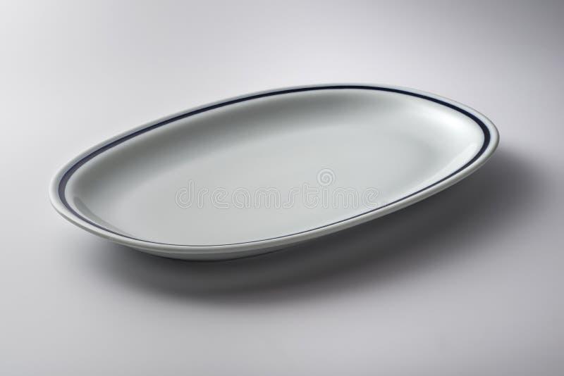 Plat ovale blanc avec la ligne bleue sur le bord image libre de droits