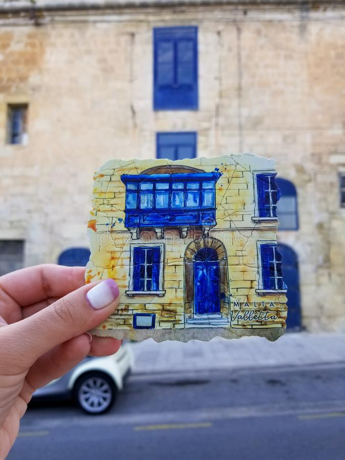 Plat pour la tasse chaude de wity de thé reproducting du balcon maltais traditionnel comme souvenir dans la main du ` s de fille images stock