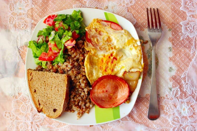 Plat pour un dîner des oeufs au plat de saucisse de sarrasin et des légumes frais bouillis photographie stock libre de droits