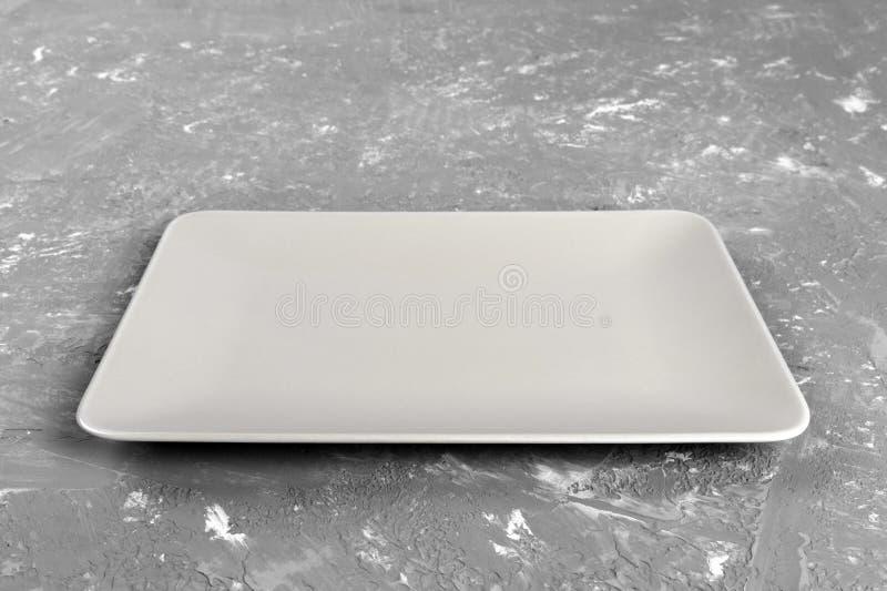 Plat rectangulaire vide sur le fond gris de table image libre de droits