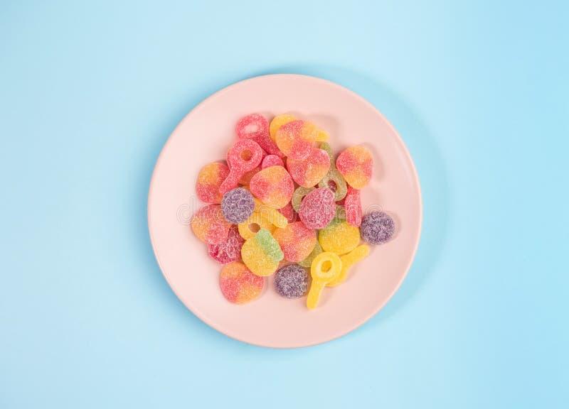 Plat rose avec les sucreries gommeuses sur le fond bleu images libres de droits