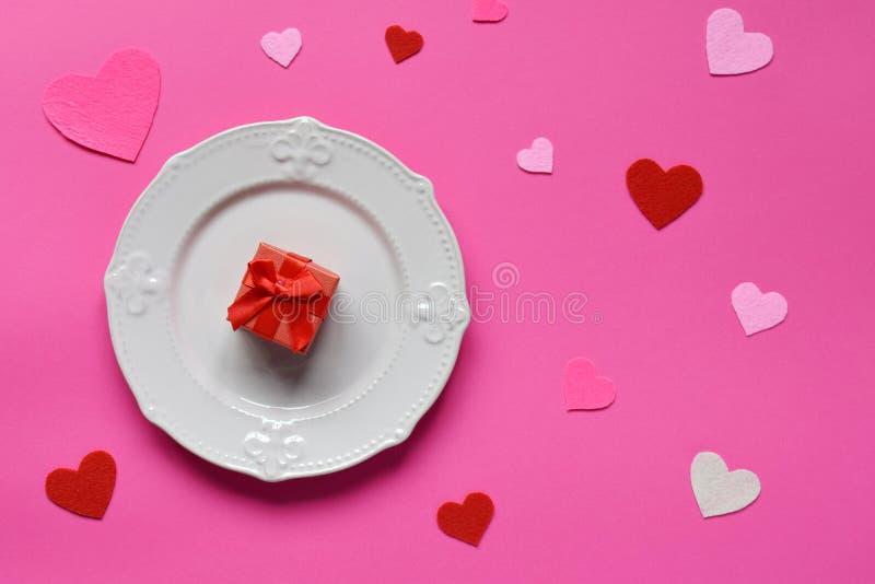 Plat rose vide, coeurs de feutre et cadeau rouge sur le fond rose St Valentine& x27 ; concept de jour de s Vue supérieure, config images stock