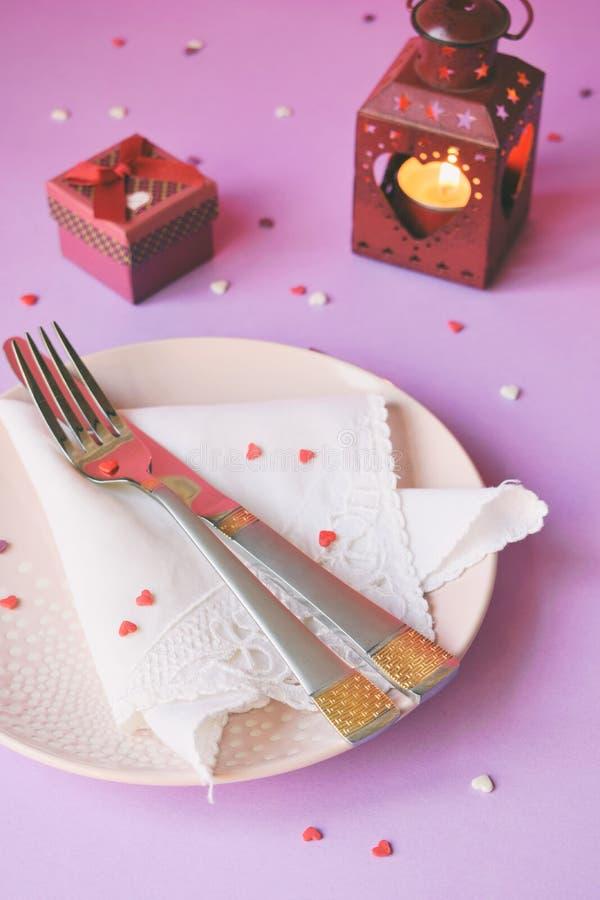 Plat rose vide, couverts, coeurs, chandeliers et cadeau rouge sur le fond rose-pourpre Concept d'arrangement de table de Saint-Va images stock