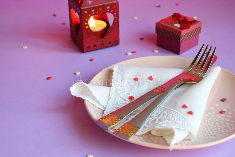 Plat rose vide, couverts, coeurs, chandeliers et cadeau rouge sur le fond rose-pourpre Concept d'arrangement de table de Saint-Va images libres de droits