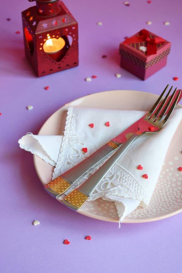 Plat rose vide, couverts, coeurs, chandeliers et cadeau rouge sur le fond rose-pourpre Concept d'arrangement de table de Saint-Va photos stock