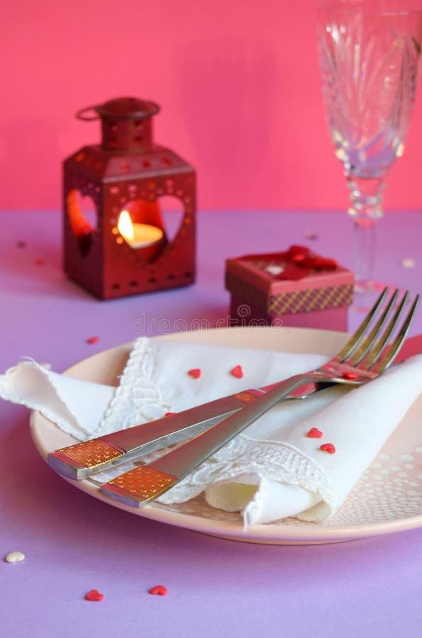 Plat rose vide, couverts, coeurs, chandeliers, verres de vin et cadeau rouge sur le fond rose-pourpre Table de Saint-Valentin de  image stock