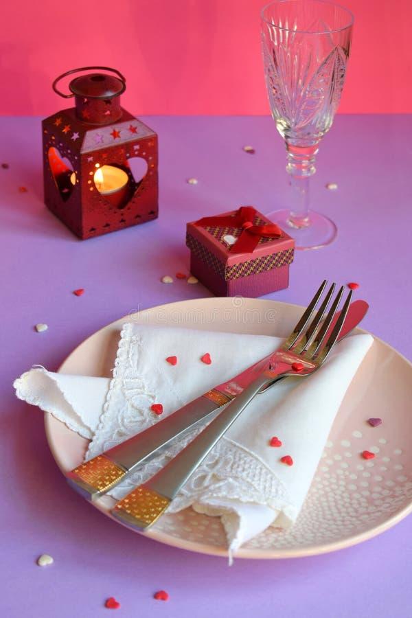 Plat rose vide, couverts, coeurs, chandeliers, verres de vin et cadeau rouge sur le fond rose-pourpre Table de Saint-Valentin de  images stock