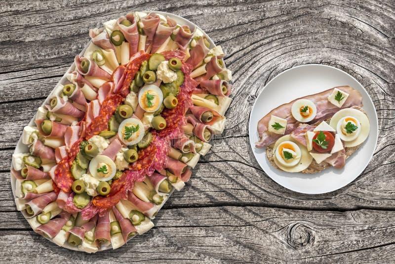 Plat savoureux d'apéritif avec l'oeuf Gammon de fromage de lard et le sandwich à tomate réglé sur le vieux Tableau en bois de jar images libres de droits