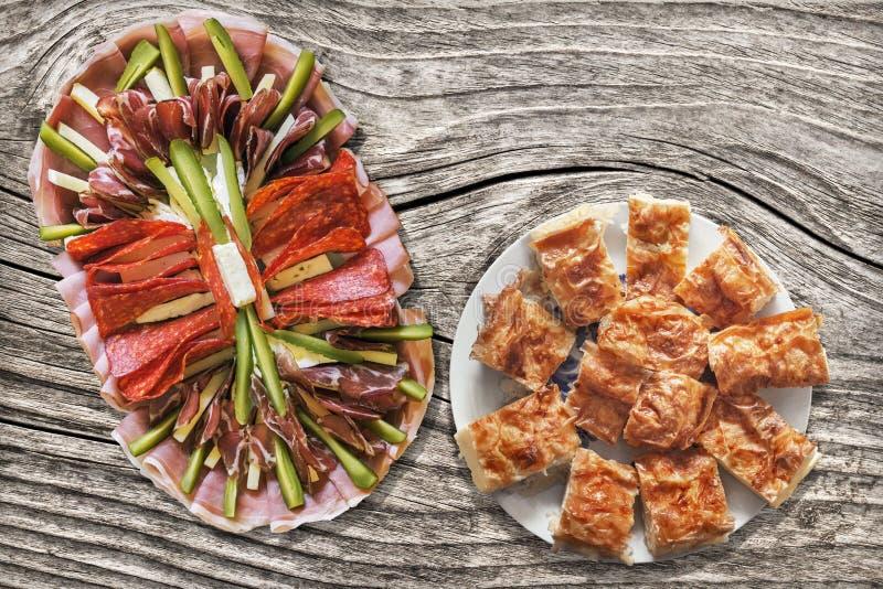 Plat savoureux d'apéritif avec les tranches serbes de tarte de fromage de Gibanica réglées sur le vieux Tableau en bois criqué no photo stock