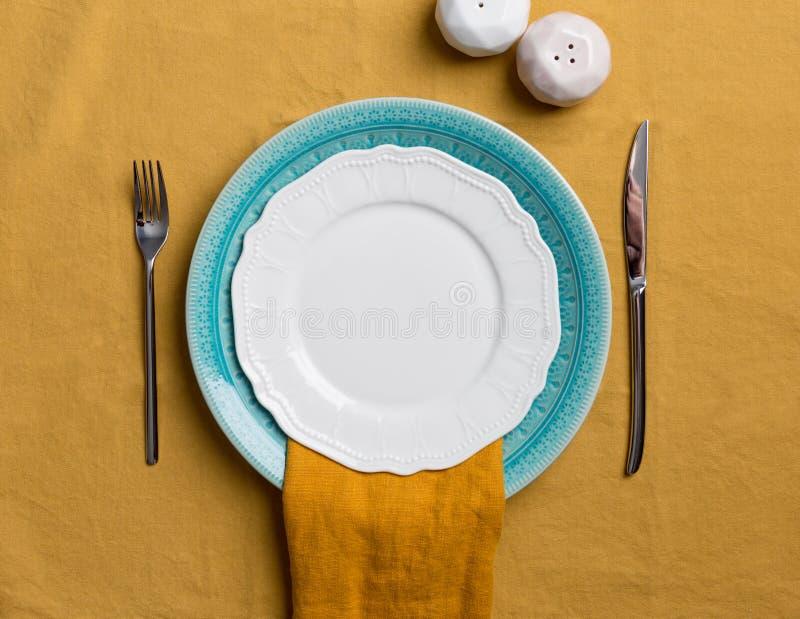 Plat servant avec le dispositif trembleur de vaisselle, de sel et de poivre sur la nappe orange image stock